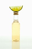A small bottle of tequila with a lime wedge on top