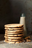 A stack of hazelnut and chocolate chip cookies in front of a bottle of milk