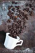 Coffee beans scattered over a rustic surface with a white coffee cup