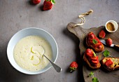 Foamy white beer soup with lemon served with sweet bruschetta with strawberries