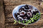 Pickled black olives with a sprig of thyme