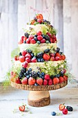 A three tier naked cake with berries on a wooden cake stand