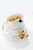 Elektrische Kartoffelschälmaschine vor weißem Hintergrund