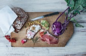Slices of bread with various toppings on a chopping board with redcurrants, purple kohlrabi and crusty bread
