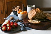 A breakfast table with bread, apricots, strawberries and walnuts