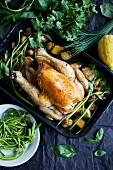 Roast chicken with potatoes, lemon, assorted herbs and wild asparagus