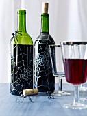 Weinflaschen gruselig dekoriert mit Spinnen und aufgemalten Spinnennetzen