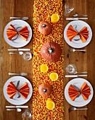 Gedeckter Tisch für Halloween dekoriert mit Kürbissen, Kerzen und Candy Corn (Aufsicht)