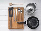 Verschiedene Küchenutensilien: Topf, Pfanne, Besteck, Sparschäler und Pfannenwender