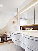 Geschwungener, weißer Waschbeckenunterbau in elegantem Designerbad