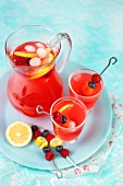 Raspberry lemonade in a glass jug and glasses