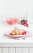 Frühstück mit Croissant, Himbeeren, Saft und Himbeermarmelade