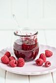A jar of raspberry jam with a spoon