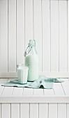 Milchflasche und ein Glas Vollmilch