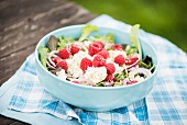 Salad with goats' cream cheese, raspberries and sesame seeds