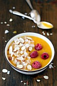A mango smoothie bowl with almonds and raspberries