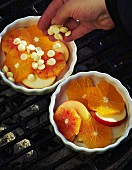 A hand putting white chocolate chips over slices of fruit in small ovenproof gratin dishes