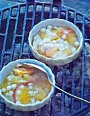 Small gratin dishes with slices of fruit and white chocolate on the barbecue