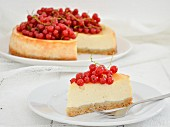A sliced cheesecake topped with fresh redcurrants