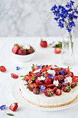 Creamy cheesecake with strawberries and edible flowers