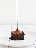 Chocolate sauce being drizzled onto a brownie