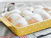 Baked sweet yeast dumplings with with raspberry jam dusted with icing sugar