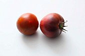 Two black tomatoes on a white surface