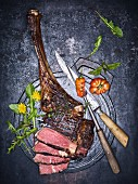 Grilled tomahawk steak, partially sliced (seen above)