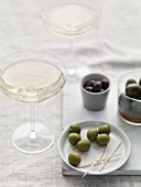 Sparkling wine in champagne cups served with assorted olives