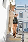 Blonde Frau in Trenchcoat, Bluse mit Stickereien, Baumwollrock mit Perlenverzierung und Wedges