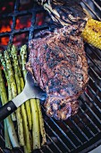 Rib-eye steak, green asparagus and corn on the barbecue