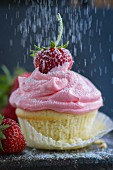 Icing sugar falling on a cupcake with strawberry cream
