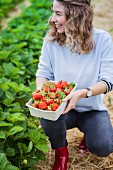 A young woman holding a cardboard box of freshly picked strawberries