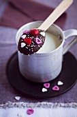 A chocolate spoon balanced on a cup of milk (Valentine's Day)