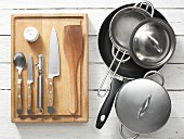 Assorted kitchen utensils: saucepans, a frying pan, an egg pricker and a knife