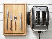 Assorted kitchen utensils: cutlery, a vegetable peeler and a toaster