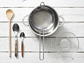 Assorted kitchen utensils: spoons, a saucepan, a sieve and a glass bowl
