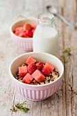 Granola with strawberries and watermelon and a bottle of oat milk