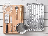 Kitchen utensils: a grater, a citrus press, a saucepan, a pastry brush and a grill tray