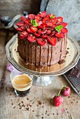 A chocolate cake with chocolate icing and sliced strawberries