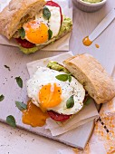 A sandwich with broad bean & feta spread, tomatoes and fried egg