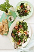 Spinach salad with radishes, cucumber, beetroot leaves, cherry tomatoes, quinoa, bread and black pepper