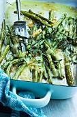 Im Ofen gebackene Bohnen mit Kräutern und geschmolzenem Parmesan in einer Backform mit Gabel und Küchentuch