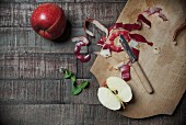 Jonared apples with peel, an apple wedge, a peeler, fresh mint and a chopping board on a wooden surface
