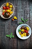 Tomatoes with fresh sage in a porcelain bowl and a basket on a wooden surface