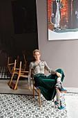 Blonde Frau mit Seidenbluse, grünem Samtrock und Pumps sitzt auf Stuhl