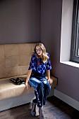 Frau in gepunkteter Schlupfbluse, blauer Samthose und blauen Pumps sitzt auf Couch