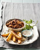 Chili con carne with potato wedges and sour cream