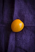 A yellow tomato on a violet cloth