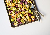 Florets of Romanesco, white cauliflower and purple cauliflower on a baking tray ready to be roasted